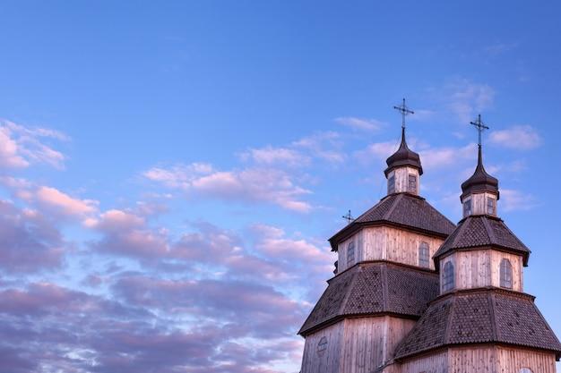 Stary drewniany nieociosany kościelny budynek i drewniany ogrodzenie przeciw niebieskiemu niebu