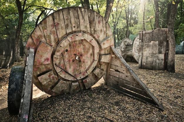 Stary drewniany okrągły budynek u podstawy do gry w paintball, za którym gracze kryją się w poszukiwaniu ratunku