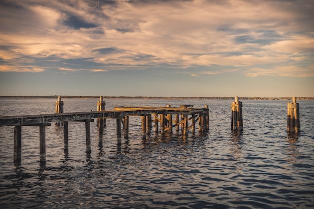 Stary drewniany pomost nad morzem w słońcu podczas zachodu słońca