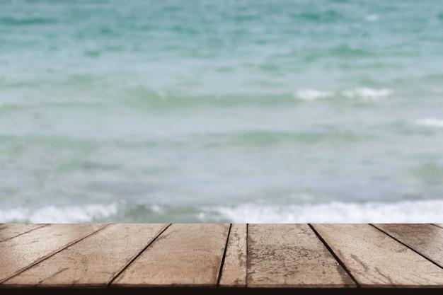 Stary drewniany stołowy wierzchołek na zamazanym plażowym tle, lata pojęcie