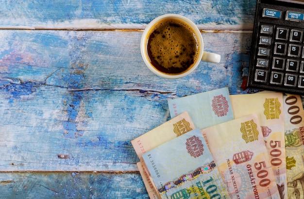 Stary drewniany węgierski forint wint nowoczesny kalkulator i filiżanka czarnej kawy