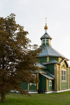 Stary drewniany xix-wieczny kościół w kolorze zielonym ze złotą kopułą i złotym krzyżem w ciepłym świetle słonecznym z platformą z zielonej trawy