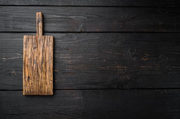 Stary drewniany zestaw płyt kuchennych, płaski widok z góry, z kopią miejsca na tekst lub jedzenie, na czarnym drewnianym stole w tle