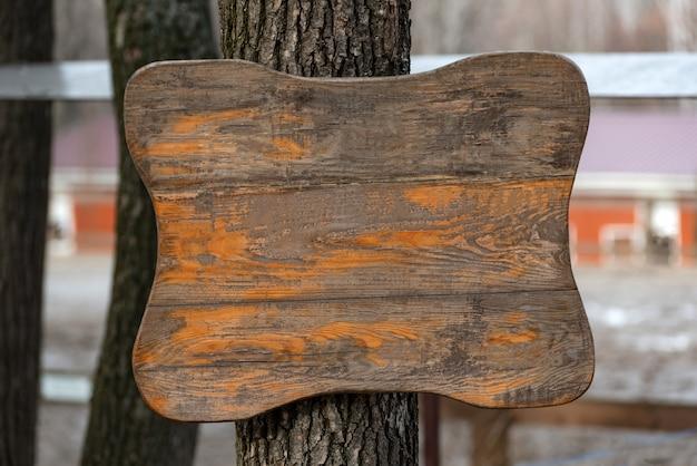Stary drewniany znak na drzewie. szorstka, porysowana powierzchnia drewniana. skopiuj miejsce.