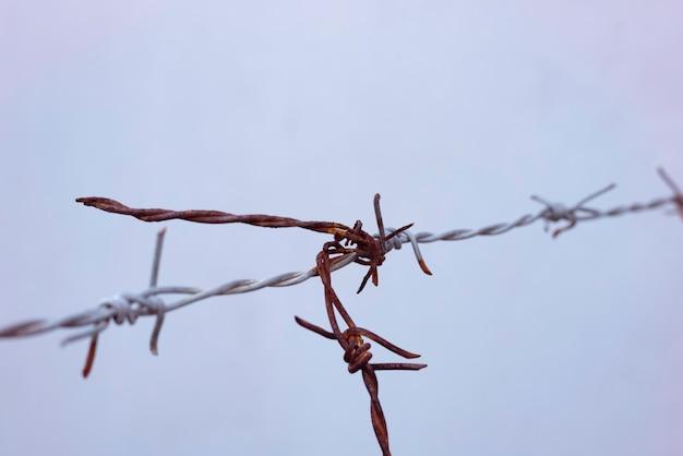 Stary drut kolczasty wiszący w powietrzu, rdza i brudny przez długi czas