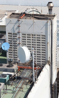 Stary duży antena satelitarna telekomunikacyjna na dachu budynku.