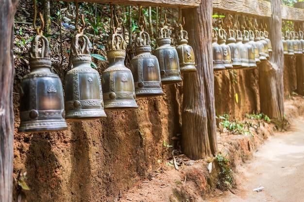Stary dzwon wisi na stalowej szynie w kamieniu ze śladami pana buddy