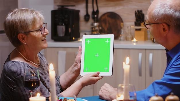 Stary emerytowany para starszych za pomocą komputera typu tablet cyfrowy na białym tle zielony makiety. ludzie w podeszłym wieku patrzący na zielony ekran szablonu chroma key, siedzący przy stole w kuchni podczas kolacji.