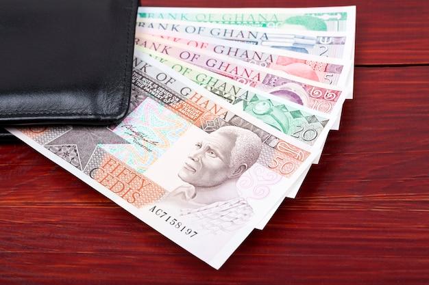 Stary ghański cedis w czarnym portfelu