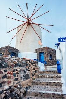 Stary grecki wiatrak na wyspie santorini w mieście oia ze schodami na ulicy santorini grecja