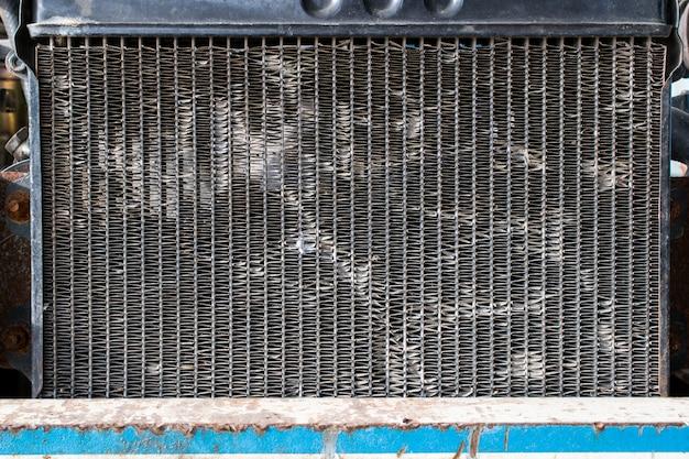 Stary grzejnik samochodowy przedstawia teksturę części samochodu i tło.
