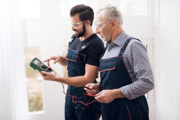 Stary i młody facet tworzą razem cyfrowy multimetr.