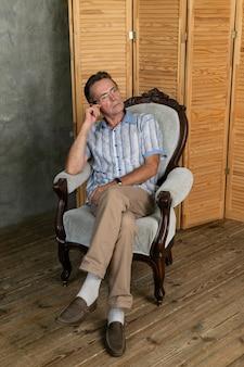 Stary inteligentny człowiek odpoczywający na fotelu