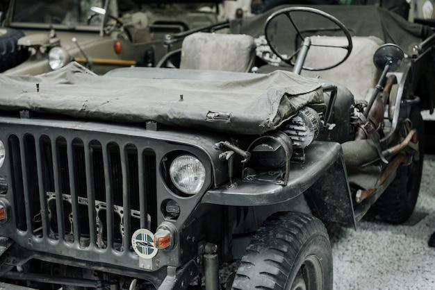 Stary jeep wojownika bez dachu pokrytego jakimś materiałem