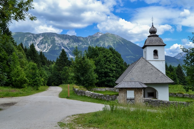Stary kamienny kościół i zielony pasmo górskie. pogodny krajobraz z niebieskim niebem z białymi chmurami.