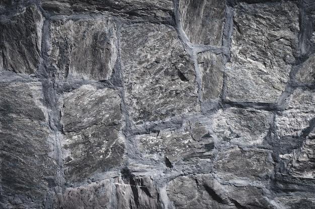 Stary kamienny mur jako tło. ściana z surowych okrągłych kamieni zamiast cegły.