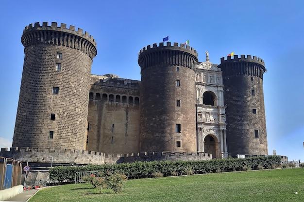 Stary kamienny zamek maschio angioino w nowoczesnym europejskim mieście. fort w neapolu. słoneczny dzień z błękitnym niebem