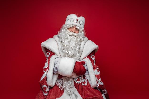 Stary kaukaski ojciec mróz w długim ciepłym płaszczu, czerwonych rękawiczkach i kapeluszu patrzy w kamerę