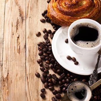 Stary kawowy garnek i filiżanka na drewnianym nieociosanym tle