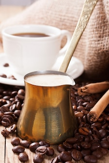 Stary kawowy garnek na drewnianym nieociosanym tle
