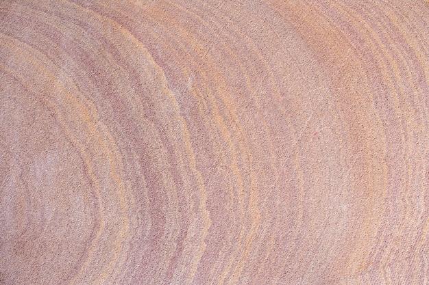 Stary kolorowy piasek kamiennej ściany tekstury tło. piętro
