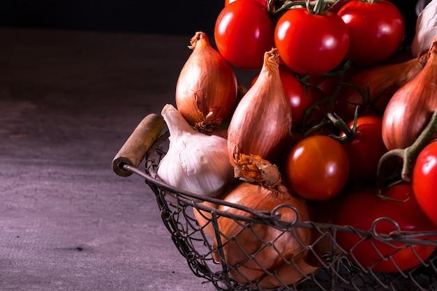 Stary kosz z cebulą, czosnkiem i pomidorami.