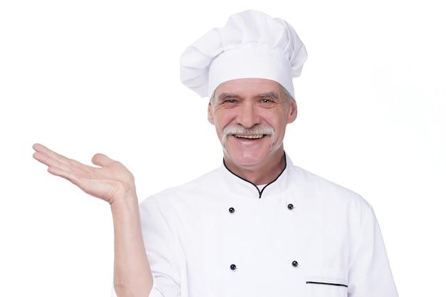 Stary kucharz na białym tle na białej ścianie