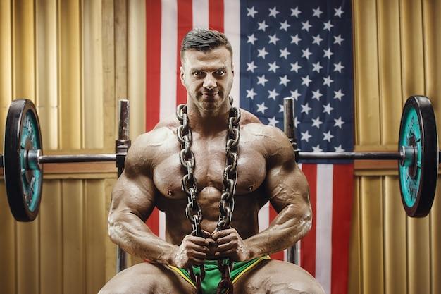 Stary kulturysta moda robi ćwiczenia w starej szkole siłowni z amerykańską flagą. przystojny sportowiec kaukaski w stylu lat 80-tych. koncepcja sportu, fitnessu i treningu z lat 80.