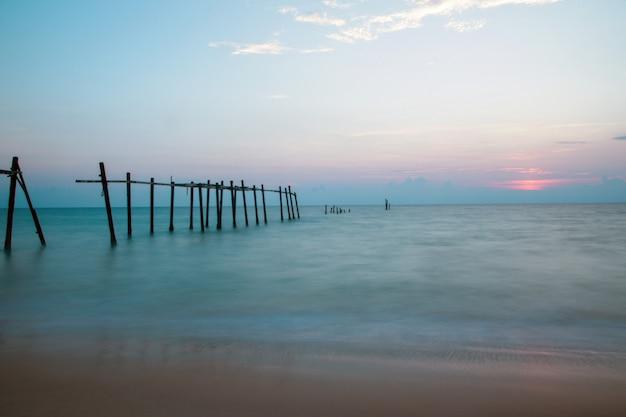 Stary łamany molo na plaży przy zmierzchu tłem.