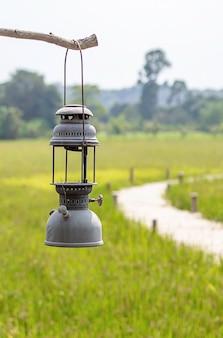 Stary latarniowy obwieszenie na drewnianych tło polach i drewnianym moscie.