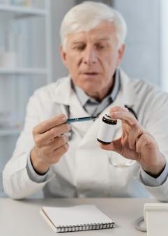 Stary lekarz płci męskiej w swoim biurze