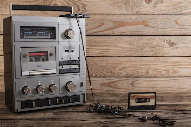 Stary magnetofon i kaseta na podłoże drewniane
