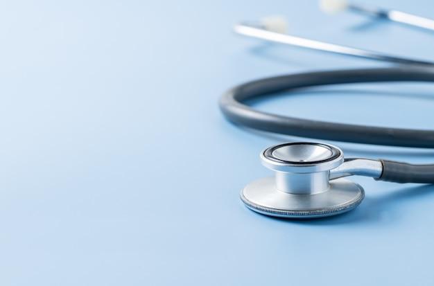 Stary medyczny stetoskop na niebieskim tle. koncepcja opieki zdrowotnej.