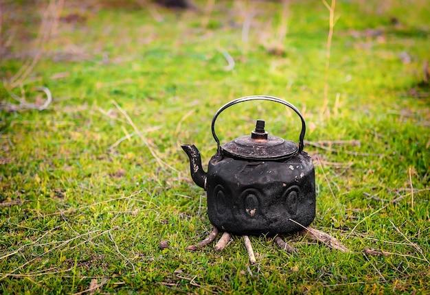 Stary metalowy czajnik na trawie