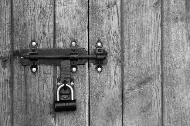 Stary metalowy zamek na tle drewnianych drzwi
