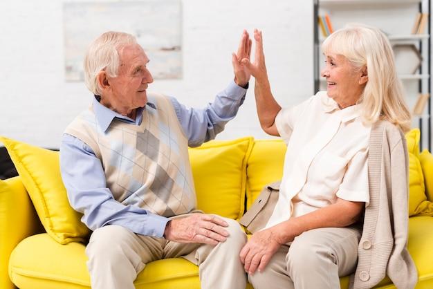 Stary mężczyzna i kobieta wysoka fiving na żółtej kanapie