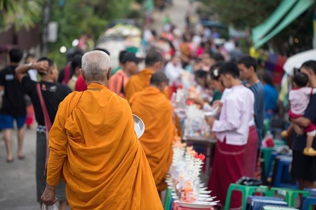 Stary mnich idący do jałmużny ludzi mon i wielu odwiedzających w wiosce sangkhla buri, kanchanaburi, tajlandia. słynna aktywność podróżnicza, która zasługuje na jedzenie rano.