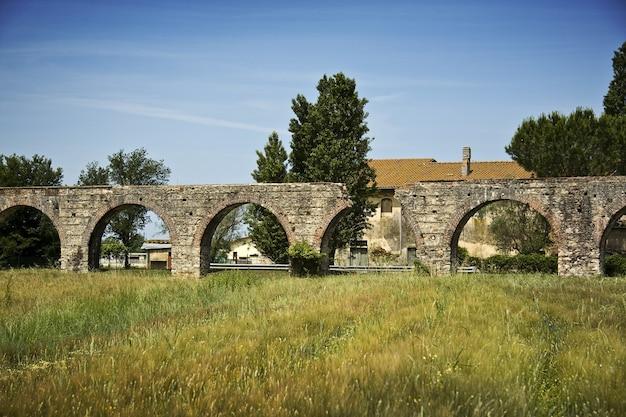 Stary most łukowy na polu trawy z drzewami i budynkiem