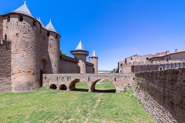 Stary most nad fosą prowadzący do zamku miasta carcassonne