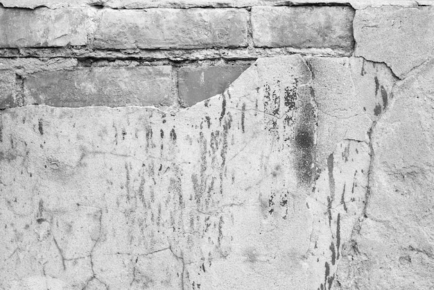 Stary mur z cegły. beton spękany. czarno-biała tekstura. tło