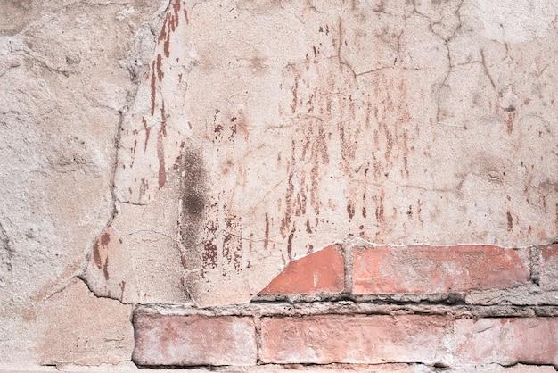 Stary mur z cegły. beton spękany. różowa, brązowa tekstura. tło