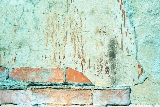 Stary mur z cegły. beton spękany. turkusowa, niebieska, brązowa tekstura. tło