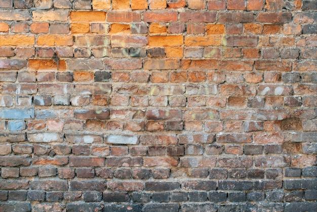 Stary mur z cegły kruszące się jako tło z bliska.
