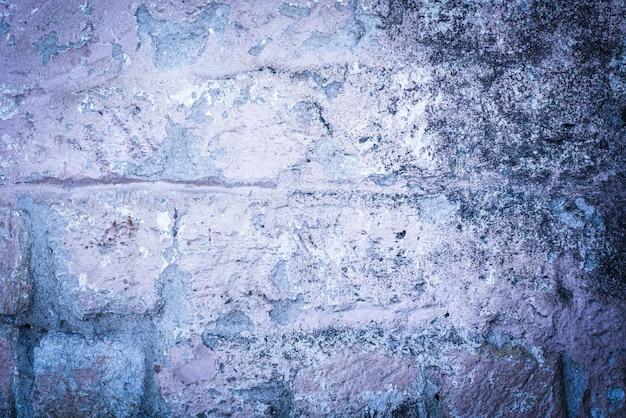 Stary mur z cegły. pęknięty beton. fioletowa, niebieska tekstura. tło. styl rustykalny, pleśń.