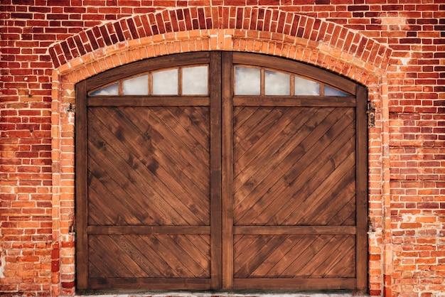 Stary mur z cegły z łukiem i drzwiami drewnianymi.