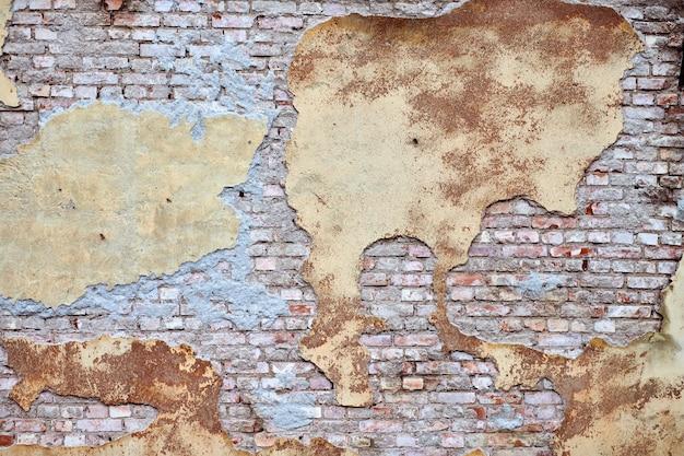 Stary mur z cegły z połamanymi sztukateriami i tynkiem.