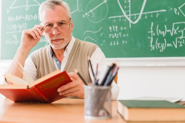 Stary nauczyciel patrzeje kamerę przy szkołą