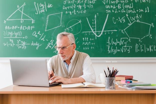 Stary nauczyciel używa laptop w sala lekcyjnej