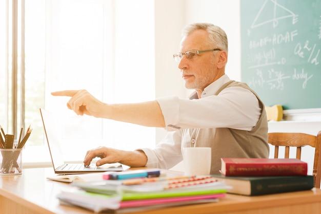 Stary nauczyciel wskazuje w sala lekcyjnej