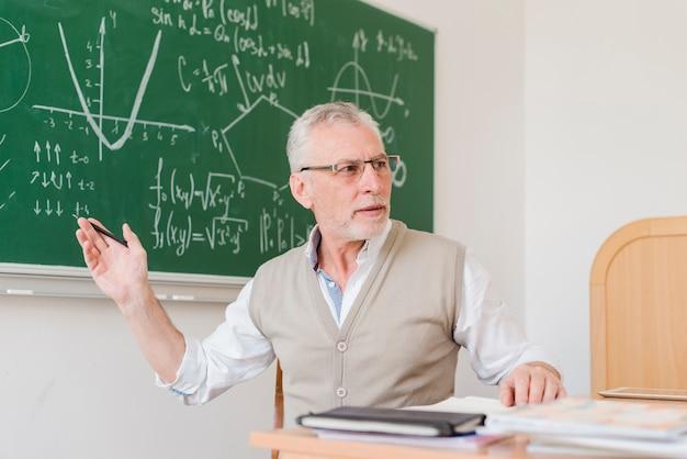 Stary nauczyciel wyjaśnia w sali wykładowej